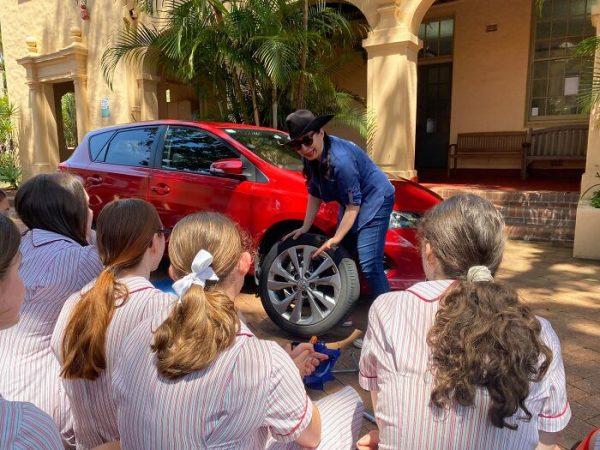 Des étudiantes apprennent à réparer une voiture